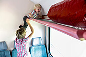 Boy  climbing up the overhead compartment inside a train, Island of Ruegen, Mecklenburg-Western Pomerania, Germany