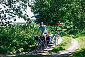 Man cycling with child transporter along a dirt track, Altefaehr, Island of Ruegen, Mecklenburg-Western Pomerania, Germany