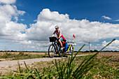 Women cycling with child transporter along a dirt track, Altefaehr, Island of Ruegen, Mecklenburg-Western Pomerania, Germany
