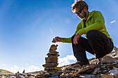 Man places stone on a cairn, Johannis hut, Virgen Valley, Tyrol, Austria