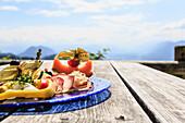 Snack plate served on the hut terrace, view towards the Inn Valley, Vorderkaiserfelden hut, Kaiserschützensteig, Kaiser Valley, Kufstein, Tirol, Austria