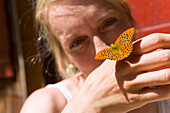 Woman holding a butterfly on hand, Plankenstein hut, Plankenstei, Rottach-Egern, Bavaria, Germany