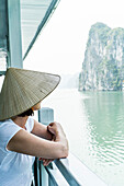 Woman on a wooden junk, enjoying the view in Halong Bay, north of Vietnam, Asia