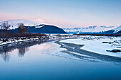 Morning alpenglow on the Kenai Mountains along the Turnagain Arm reflects in the outfall of Portage Creek, Southcentral Alaska, Winter