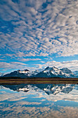 Alaganik slough reflecting the Chugach Mountains and cirrocumulus clouds in the morning, Chugach National Forest, Cordova, Southcentral Alaska, Spring