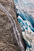 A waterfall flows down bedrock on the edge of Mendenhall Glacier, Juneau, Southeast Alaska, Summer