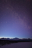 Night time view of Mt. McKinley with a star filled sky, the Milky Way, and a shooting star overhead, Denali State Park, Southcentral Alaska, Winter