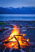 Campfire at dusk on a remote coastal beach in Goose Cove with Fairweather Range in the background, Muir Inlet, Glacier Bay National Park & Preserve, Southeast Alaska, Summer