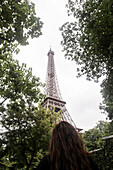 Young Woman Looking Up Through Trees at Eiffel Tower, Paris, France