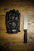 Pair of Black Leather Gloves and Knife on Wood Floor