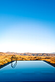 An infinity water pool with steps with a view over the Andalucian mountains in Spain. Late summer afternoon.