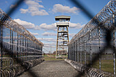 Prison fence, watch tower and barbed wire at Correctional Facility. High security.