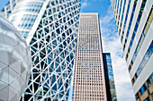 Skyscrapers in Tokyo's Shinjuku District. View up to the tall modern architectural landmarks from street level.