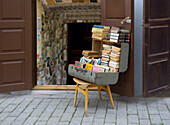 An antique shop on a street in a town in Estonia. A suitcase of second hand books in a suitcase on a chair.