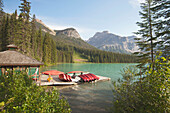 A view from a waterfront pier over the landscape of the Rocky Mountains surrounding the Emerald Lake and the brightly coloured waters of the lake, Canoes and kayaks for hire