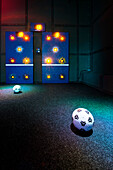 Soccer target game on one of the walls in a dimly lit active gaming center