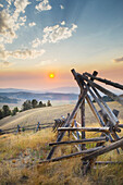 Strong log stock fence in ranch lands, Sunset over the mountains and valleys of Montana