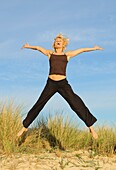 Mature Woman Jumping For Joy On Beach