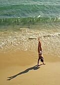 Woman Doing Handstand On Beach