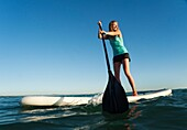 A Woman Paddling While Standing On A Surf Board Off Dos Mares Beach, Tarifa, Cadiz, Andalusia, Spain
