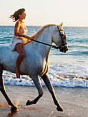 A woman riding a white horse on the beach at sunset by the ocean, tarifa cadiz andalusia spain