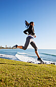 A young woman running by the water's edge, gold coast queensland australia