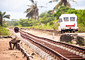 Child sitting on the edge of railway lines, looking at a train, Madagascar, Africa