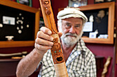 blocked for illustrated books in Germany, Austria, Switzerland: Master carver Brian Flintoff with wooden carved, mythical figures on a flute, Instrument maker, Maori Music, South Island, New Zealand