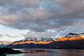 letzte Lichtstrahlen der untergehenden Sonne auf einem Gebirgszug am Lake Wakatipu,Bergkulisse bei Queenstown,Streiflicht,Wolkenspalte,Queenstown,Südinsel,Neuseeland