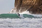 Surfer near cliffs, east coast, Castle Point, North Island, New Zealand