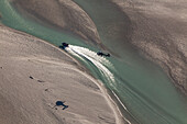 Aerial view of a jetboat speeding in a river, followed by a helicopter, Queenstown, Otago, New Zealand