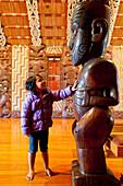 Little girl touching Maori carving, Traditional meeting house at Waitangi representing all tribes, Maori Culture, Te Whare Runanga, North Island, New Zealand
