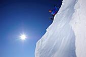 Skifahrer auf Schneewechte macht sich zur Abfahrt bereit, Großer Rettenstein im Hintergrund, Brechhorn, Kitzbüheler Alpen, Tirol, Österreich
