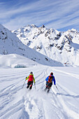 Two skiers downhill skiing from mount Wildspitzer on glacier, Oetztal Alps, Tyrol, Austria