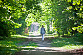 Woman walking along the way in the wood, Vienna, Austria
