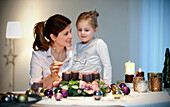 Mother and daughter  lighting candle on an Advent wreath, Styria, Austria