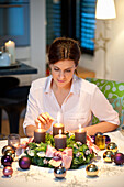 Mid adult woman lighting candles on an Advent wreath
