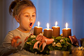 Girl (4 years) will blowing out candles of an Advent wreath