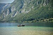 Man, woman and dog with boat at Lake Bohinj, Triglav National Park, Julian Alps, Gorenjska, Slovenia