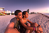 Young latino couple watching the sunrise on the beach, South Beach, Miami, Florida, USA