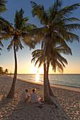Couple sitting at sunrise on Key West Smathers Beach, Key West, Florida Keys, Florida, USA
