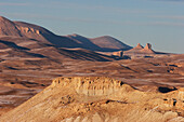 Barren rock formations on a plateau in the Band-i-Amir area lit by the late afternoon sun, Bamian Province, Afghanistan