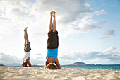 Hawaii, Oahu, Lanikai, Young couple doing yoga, stay in a headstand position on the beach.