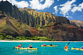 Hawaii, Kauai, Na Pali Coast, Group of kayakers paddling along coastline, Beautiful mountain ridges in background. Editorial Use Only.