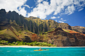 Hawaii, Kauai, Na Pali Coast, Man kayaking along coastline, Beautiful mountain ridges in background. Editorial Use Only.