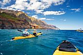 Hawaii, Kauai, Na Pali Coast, Group of kayakers paddling along coastline, Beautiful mountain ridges in background. Editorial Use Only.
