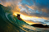Hawaii, Maui, Makena - Big Beach, Skimboarder carving turquoise wave, Sunset light.