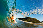 Hawaii, Maui, Makena - Big Beach, Boogie boarder riding barrel of beautiful wave, Sunrise light.