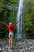 Hawaii, Maui, Waimoku Falls, Female hiker at base of waterfall.
