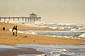 California, Manhattan Beach, Surfers on the shoreline checking the waves